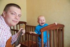 Il pap? gioca la chitarra per consolare suo figlio gridante fotografia stock