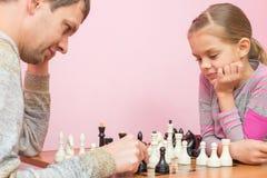 Il papa e la figlia di sette anni che giocano scacchi immagini stock libere da diritti