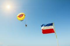 Il paracadute vola contro un contesto dei cieli blu soleggiati e della t fotografia stock libera da diritti