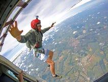 Il paracadutista coraggioso con il casco rosso salta dell'aereo Fotografia Stock Libera da Diritti