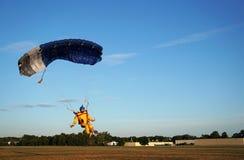 Il paracadutista sotto un piccolo baldacchino blu di un paracadute sta atterrando sopra fotografie stock libere da diritti