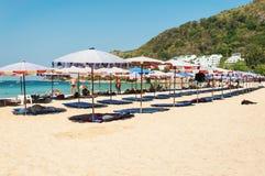 Il parasole e qualche gente si rilassano sulla spiaggia Fotografia Stock