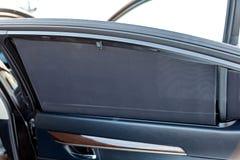 Il parasole sul vetro della porta posteriore del primo piano di colore del nero dell'automobile protegge maglia strutturata dei r fotografia stock libera da diritti