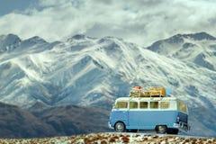 Il parcheggio di viaggio dell'automobile sulla strada parteggia contro il bello mounta della neve Fotografia Stock