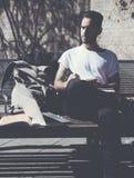 Il parco di seduta d'uso della città della maglietta bianca dell'uomo barbuto della foto ed estrae il blocco note Studiando all'u Fotografia Stock Libera da Diritti