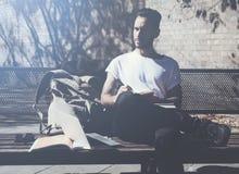 Il parco di seduta d'uso della città della maglietta bianca dell'uomo della foto e scrive il messaggio Studiando all'università,  Fotografia Stock Libera da Diritti