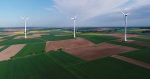 Il parco eolico sta in campo verde, generatore eolico sui precedenti del cielo blu e nuvole di galleggiamento, soleggiati stock footage