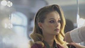 Il parrucchiere è spruzzare hairspay sull'acconciatura di bella signora nel salone di bellezza stock footage