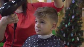 Il parrucchiere asciuga il bambino dei capelli archivi video