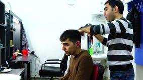Il parrucchiere asciuga il ragazzo dei capelli un Hairdryer stock footage