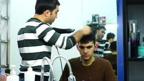 Il parrucchiere asciuga il ragazzo dei capelli un Hairdryer archivi video