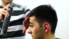 Il parrucchiere asciuga il ragazzo dei capelli un Hairdryer video d archivio
