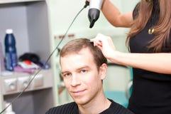 Il parrucchiere asciuga il tirante dei capelli Fotografie Stock