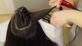 Il parrucchiere asciugacapelli i capelli bagnati delle ragazze con un asciugacapelli e pettina il pettine video d archivio