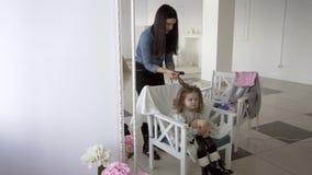Il parrucchiere che fa i riccioli facendo uso di un ferro dei capelli alla piccola ragazza graziosa è bello archivi video