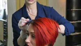 Il parrucchiere colora il primo piano dei capelli del ` s del cliente video d archivio