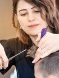 Il parrucchiere del barbiere taglia il giovane in un salone di bellezza vista al parrucchiere con luce solare immagini stock