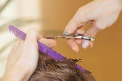 Il parrucchiere del barbiere taglia il giovane in un salone di bellezza Vista posteriore immagine stock