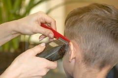 Il parrucchiere del barbiere taglia il giovane in un salone di bellezza Vista posteriore fotografie stock