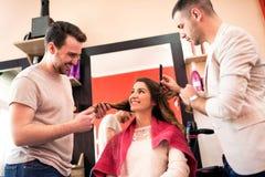 Il parrucchiere del gruppo prende la cura dei capelli dei clienti al salone di bellezza fotografia stock