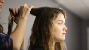 Il parrucchiere del primo piano fa l'acconciatura per la giovane donna nel salone di bellezza stock footage