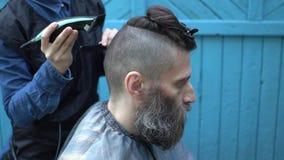 Il parrucchiere della donna che rende a pantaloni a vita bassa il taglio di capelli maschio per il mezzo ha invecchiato l'uomo co archivi video