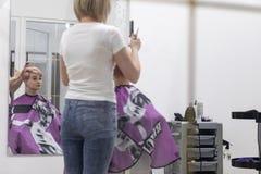 Il parrucchiere della donna fa l'acconciatura in un salone di bellezza fotografie stock