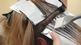 Il parrucchiere dello stilista fa la coloritura di capelli, blonding, colorante le radici dei capelli archivi video