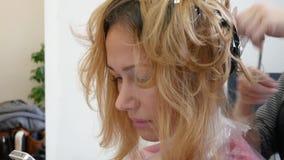 Il parrucchiere dello stilista fa la coloritura di capelli, blonding, colorante le radici dei capelli video d archivio