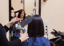 Il parrucchiere fa allinea i capelli con il ferro dei capelli ad una ragazza, castana in un salone di bellezza Immagini Stock