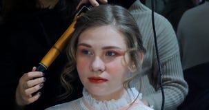 Il parrucchiere fa i hairdress al bello modello prima del photosession stock footage
