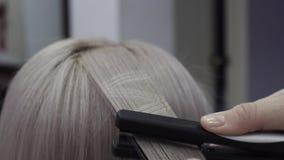 Il parrucchiere fa i modelli sui mèche di capelli facendo uso di un rivestire di ferro archivi video