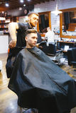 Il parrucchiere fa l'acconciatura per un giovane Fotografia Stock Libera da Diritti