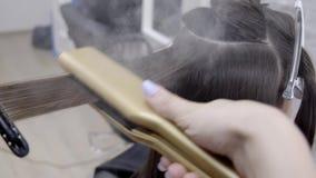 Il parrucchiere fa la laminazione dei capelli in un salone di bellezza per una ragazza con capelli castana stock footage