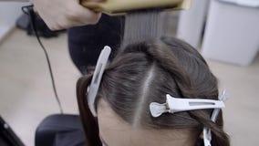 Il parrucchiere fa la laminazione dei capelli in un salone di bellezza per una ragazza con capelli castana video d archivio