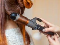 Il parrucchiere fa la ragazza dell'acconciatura con capelli rossi lunghi in un salone di bellezza fotografia stock