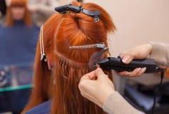 Il parrucchiere fa le estensioni dei capelli ad una giovane, ragazza dai capelli rossi, in un salone di bellezza fotografia stock libera da diritti