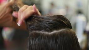 Il parrucchiere fa un'acconciatura per una donna Primo piano di taglio di capelli Forbici e pettine ai bei capelli dello stilista video d archivio