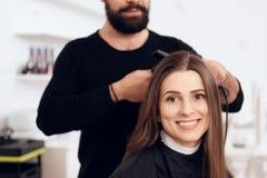 Il parrucchiere femminile raddrizza i capelli marroni alla donna graziosa che utilizza il ferro dei capelli nel salone di bellezz immagini stock libere da diritti