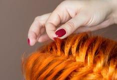 Il parrucchiere intreccia la treccia di una ragazza dai capelli rossi fotografia stock libera da diritti