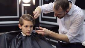 Il parrucchiere maschio taglia un giovane ragazzo in un parrucchiere video d archivio