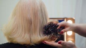 Il parrucchiere mette i capelli con un pettine per signora senior che si siede prima dello specchio archivi video