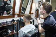 Il parrucchiere mostra il breve taglio di capelli con lo specchio al cliente soddisfatto bello nel salone professionale di lavoro immagini stock libere da diritti