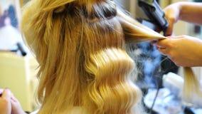 Il parrucchiere professionista asciuga l'asciugacapelli delle ragazze dei capelli video d archivio