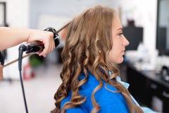 Il parrucchiere professionista che usando il ferro di arricciatura per i capelli arriccia Fotografia Stock