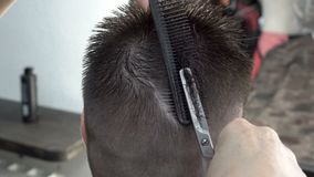 Il parrucchiere rende ad un uomo un breve taglio di capelli in parrucchiere e taglia i suoi capelli sul retro delle forbici cape video d archivio