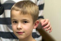 Il parrucchiere sta tagliando i capelli di un ragazzo del bambino nel negozio di barbiere Fotografie Stock