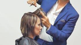 Il parrucchiere taglia i capelli ad una ragazza con forbici professionali stock footage
