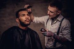 Il parrucchiere tatuato professionista antiquato fa un taglio di capelli ad un cliente afroamericano su buio strutturato immagini stock