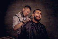 Il parrucchiere tatuato professionista antiquato fa un taglio di capelli ad un cliente afroamericano su buio strutturato fotografia stock libera da diritti